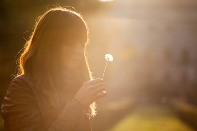 woman smiling holding dandelion
